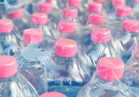 Pink screw cap of  water bottles in plastic wrap Imagens - 32932699
