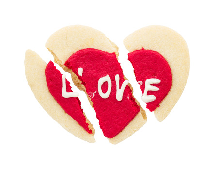 Cracked red heart shaped cookie isolated on white background photo