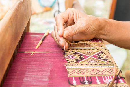 전통적인 태국 실크를 짜는 여자 손