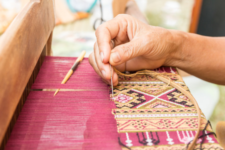 Woman hand weaving traditional thai silk