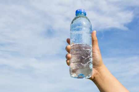 woman in water: hand holding water bottle on cloud and sky background