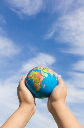 hands holding globe: hands holding globe with cloud and sky background Stock Photo