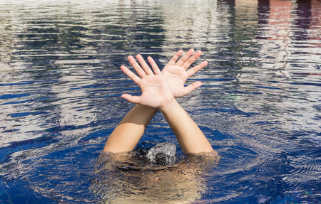 gesticulate: Hand of drowning man in a swimming pool