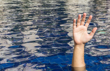 in need of space: Hand of drowning man in a swimming pool