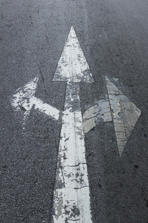 fade: Three white arrows sign on asphalt road