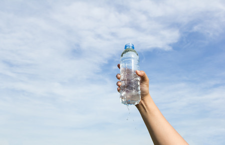 water bottle: hand holding water bottle on cloud and sky background