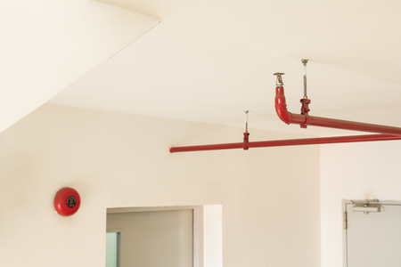Fire sprinkler and red pipe hanging on ceiling of building