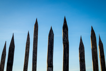 Spiky wooden fence on blue sky background Foto de archivo - 119078469