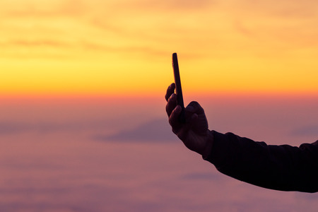 Silhouette of man hand taking a photo on sunrise with mobile phone