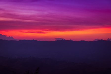 silhouette of mountains on orange and purple sky background