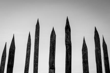 alter stacheliger Holzzaun auf Himmelshintergrund, Schwarzweißfoto