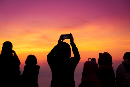 silhouette of people take a photo of gloden and purple sky background