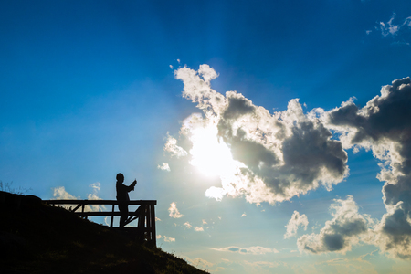 silhouette of man holding smartphone and take a photo of sun and clouds with blue sky background Imagens