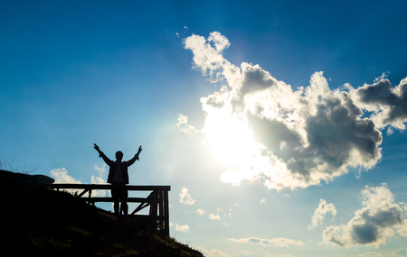 silhouette of man raise his hands on mountain in the sunlight and clouds with blue sky background Imagens
