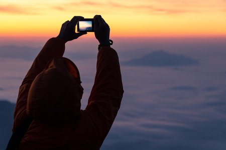 silhouette of person in orange jacket take a photo of sunrise and fog
