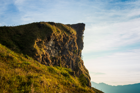 High cliff and blue sky with grass foreground in the morning at phu chifa, chaing rai, thailand Imagens