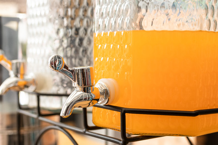 Orange juice in Glass jar with stainless steel faucet Imagens