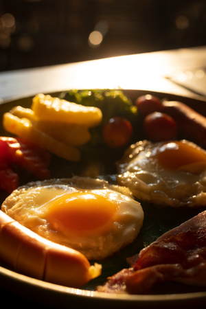 fried eggs, sausages and vegetable on plate with sunlight in the morning , american breakfast
