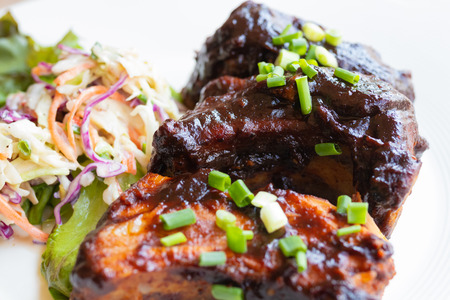 baked pork ribs with barbecue sauce on white plate
