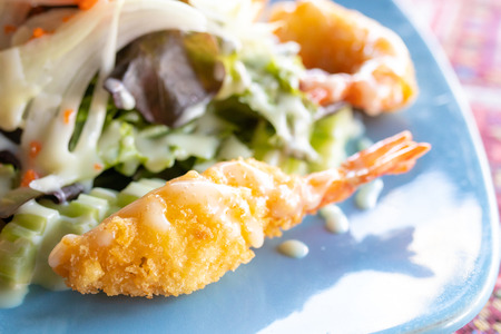 fried shrimp tempura and vegetables salad in salad dressing