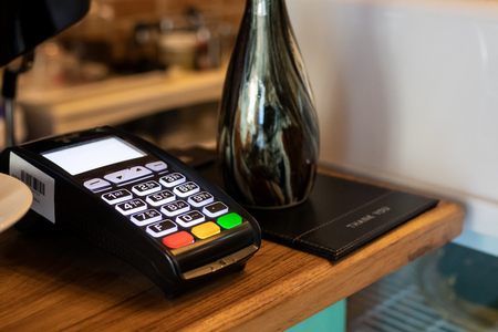 payment terminal or credit card machine on table at cafe