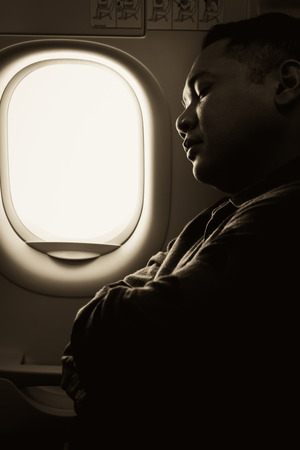 young man sleeping in an airplane window seat, warm monotone