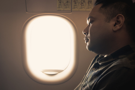 man absent-minded in an airplane window seat