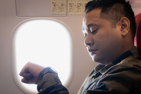 Man looking time on hand watch while an airplane window seat