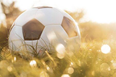 Close up of football on grass with bokeh and golden sunlight background