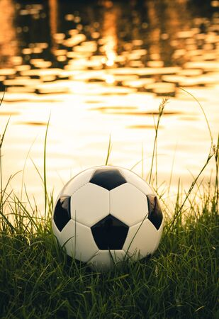 Soccer ball on grass with sunlight reflection water surface background Stockfoto