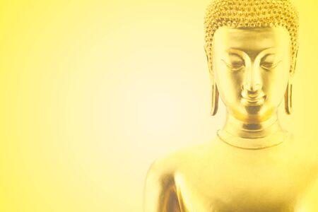 visage doré de la statue de bouddha sur fond jaune dégradé