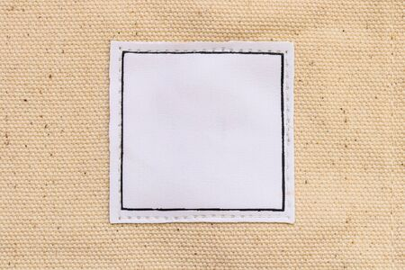 blank white square shape leather label on brown canvas fabric background Stock Photo