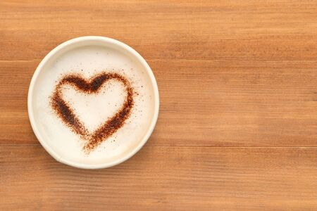 Top view of cup of cappuccino coffee with  heart shaped chocolate powder on brown wooden table background