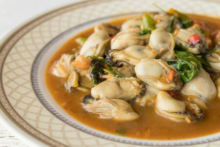 Stir fried oyster with basil leaves on dish, Thai seafood