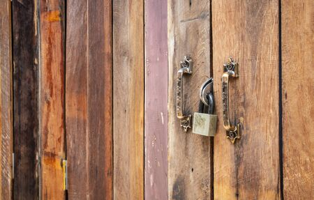 Closed old vintage wooden plank door with padlock