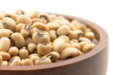 Close-up of black eyed pea beans or cowpeas in wooden bowl on white background