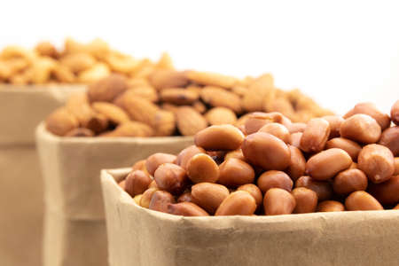close up of red skin peanuts in brown paper bag on a white background