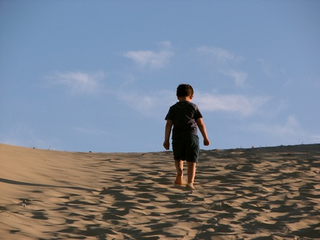 lonely child: Young, lonely boy trekking in the sands of the dunes Stock Photo