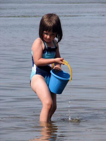 Baby girl playing in the lake, splashing water and carrying a blue bucket Stock Photo - 9980841
