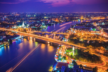 Bangkok city skyline and Chao Phraya River, located near Phra Phuttha Yodfa Bridge under twilight evening sky.