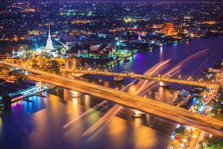 Bangkok city skyline and Chao Phraya River, located near Phra Phuttha Yodfa Bridge under twilight evening sky.