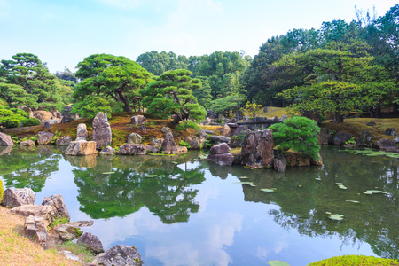 Ninomaru garden, a traditional Japanese Zen garden in summer season with Bonsai trees, stones, pond and rock bridge. at Nijo Castle (Nijojo), famous historic site and tourist destination in Kyoto, Japan.