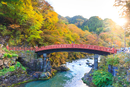 View of Shinkyo bridge (red bridge) in autumn season, one of famous travel destination of Nikko, Japan.