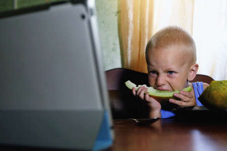 Little kid eating melon on the table and looking to the screen photo