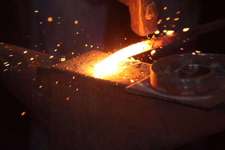 forge: Hands of smith with hammet and steel stick on the anvil Stock Photo