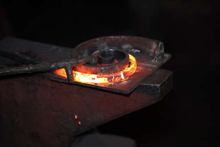 special steel: Preparing  some figure from hot steel stick on the anvil with special tool Stock Photo