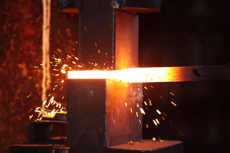forge: smith work  with hammet and steel stick on the anvil