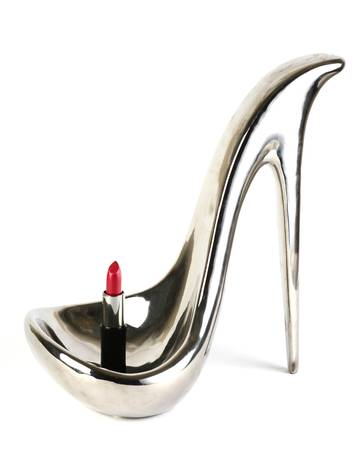 Silver shoe with a lipstick made from metal on whiye background photo