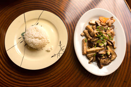 doufu: Fried black mushrooms with tofu and rice on the table