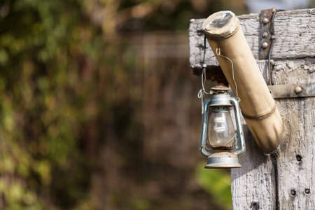 old lamp: old lamp hanging on the old wooden holder
